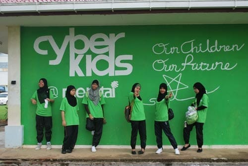 Cyberkids participants posed at the school's computer lab wall which has been painted with Cyberkids logo